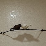 "One of many decorative ""2 birds"" wall pieces conveying the bar's theme."