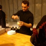 A bartender is making a beer-based mixed drink.