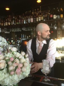 Pink-clad mixologist shaking things up in front of the blossoms