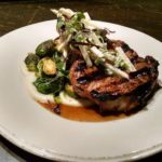GRILLED PORK CHOP: Celery root puree, vadouvan-scented Brussels sprouts, pink lady apples